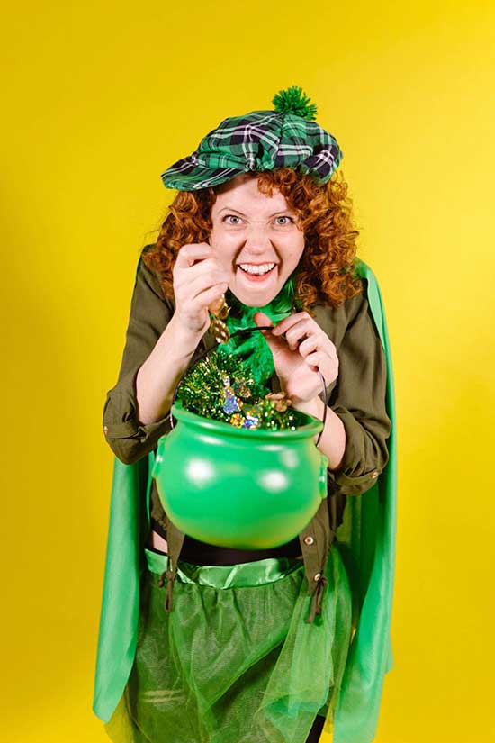 A woman dressed in green as a leprechaun holding a bucket of candy against a yellow background.